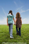 Two young multi-ethnic girls holding hands and walking away from camera.